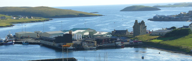 Blacksness pier with the Scalloway castle and North Atlantic Fisheries College on the headland beyond